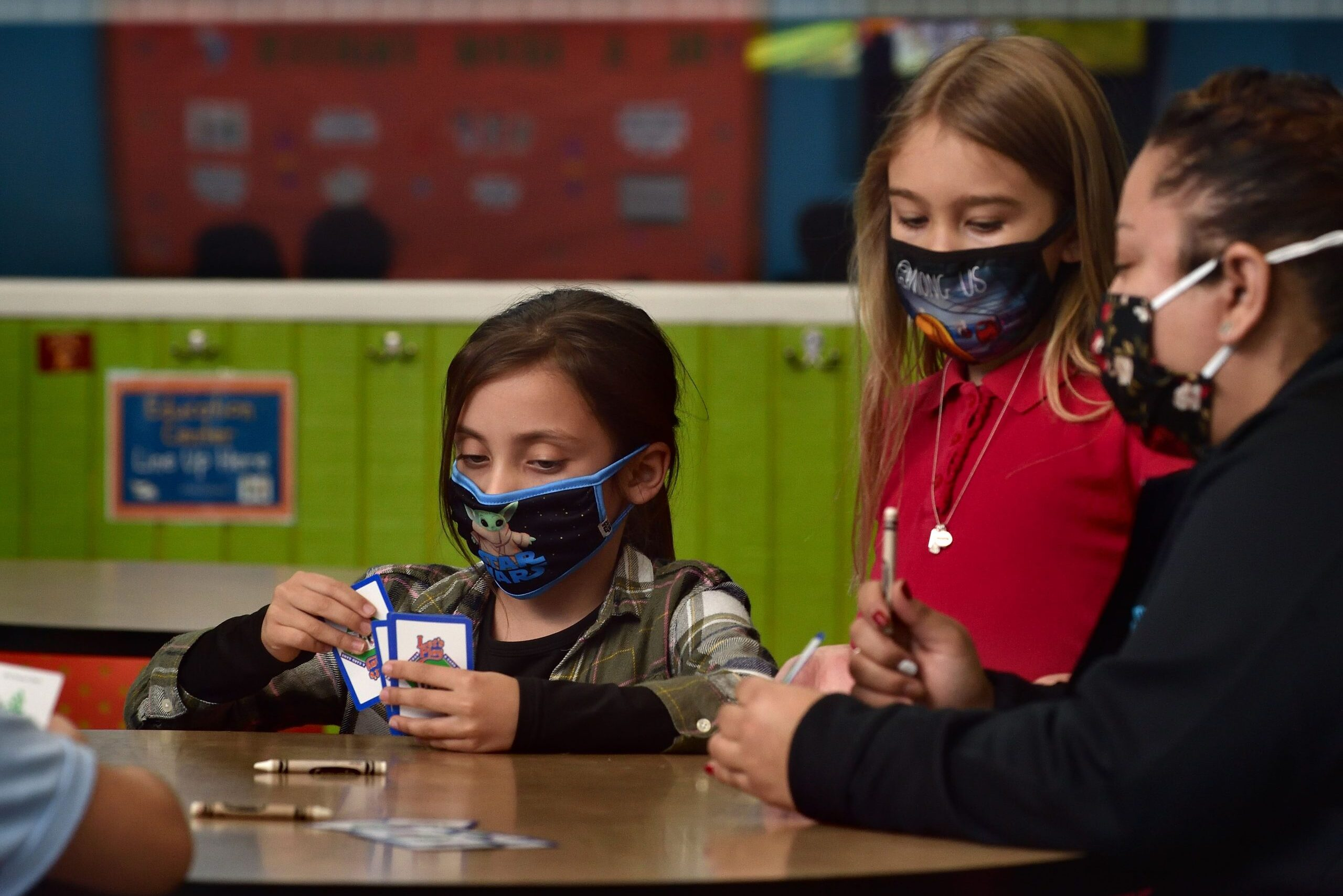 school-age girls wearing masks play cards
