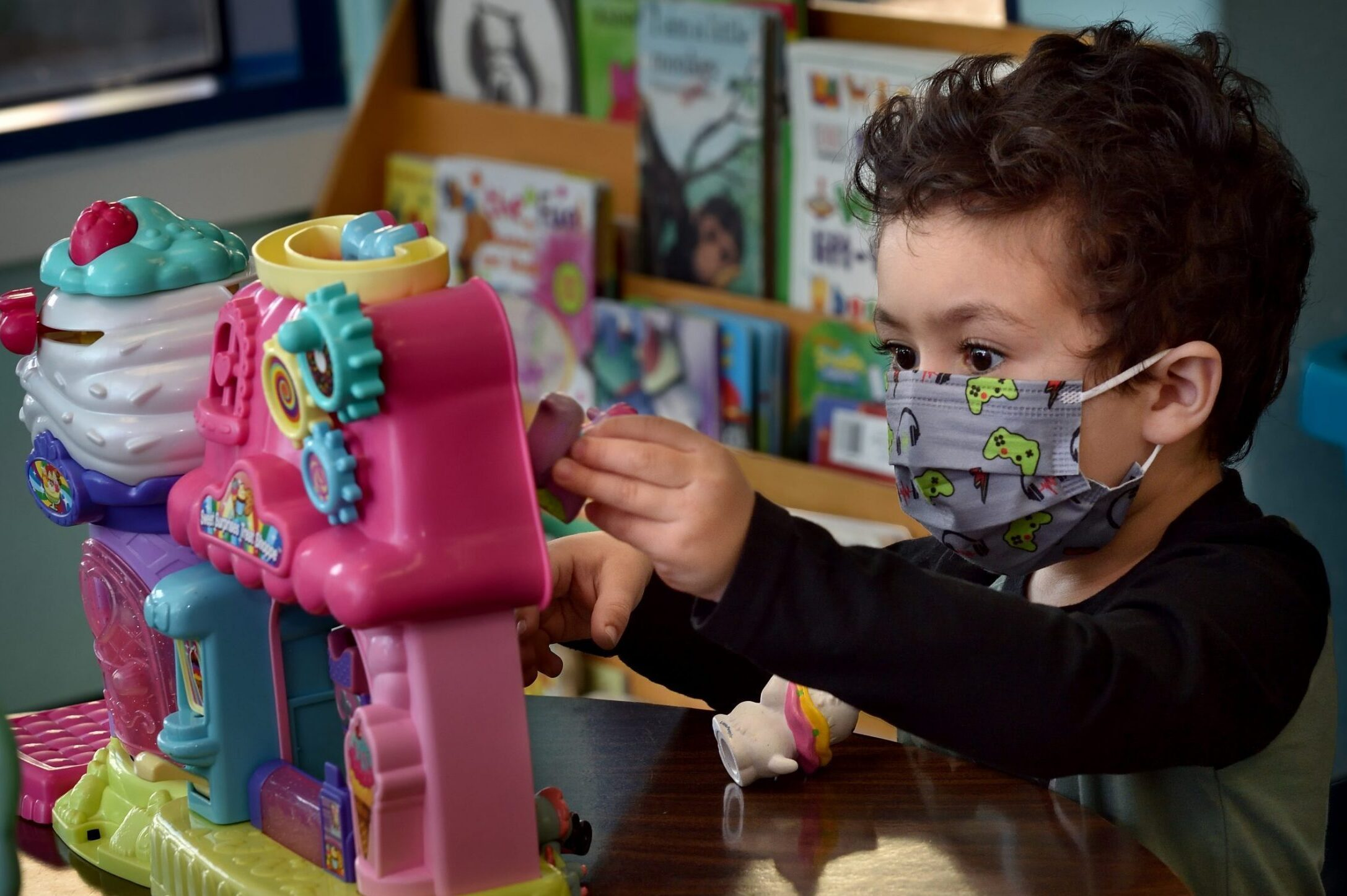 a young boy wearing a mask plays with toys in a preschool