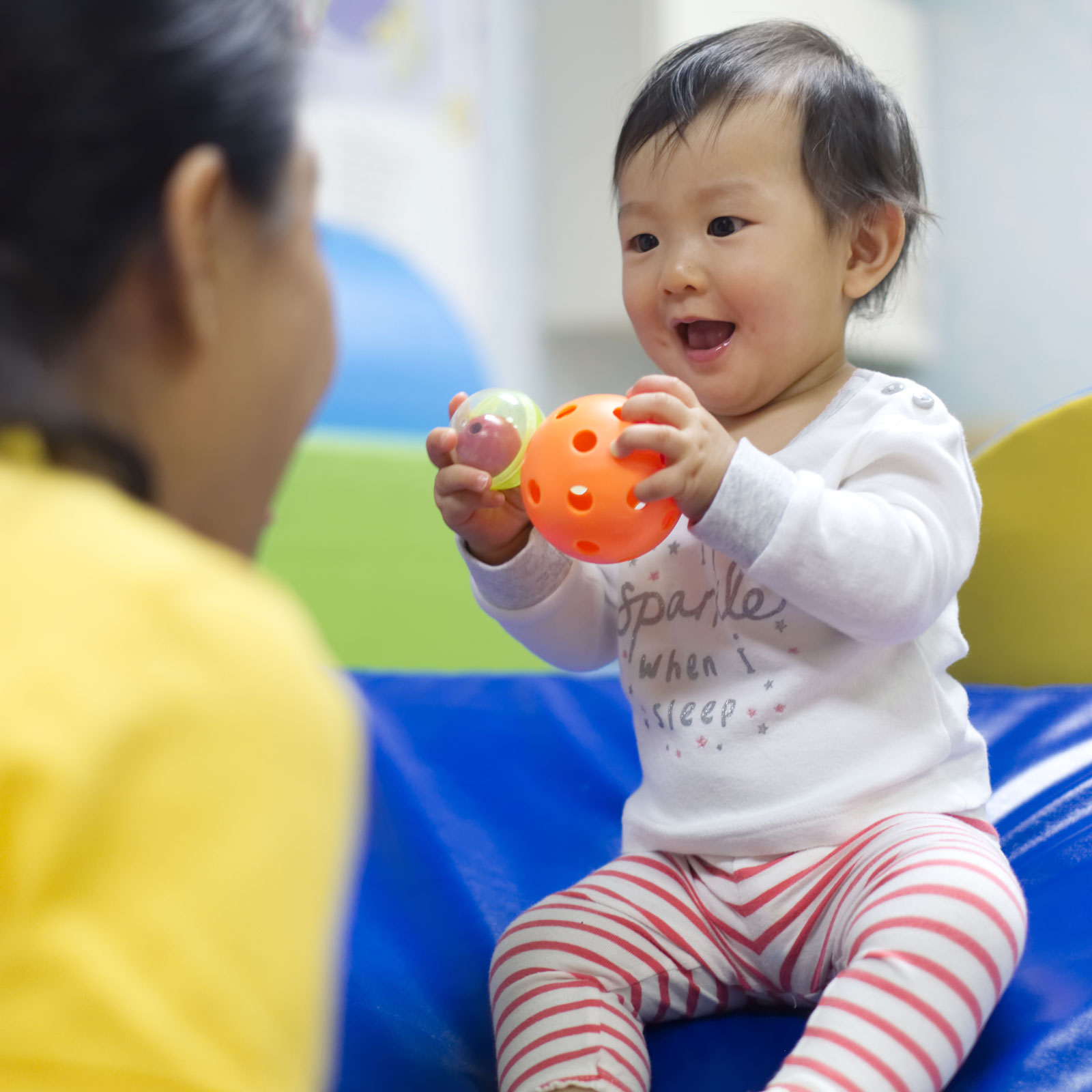 Smiling baby holding a ball and looking at her mom
