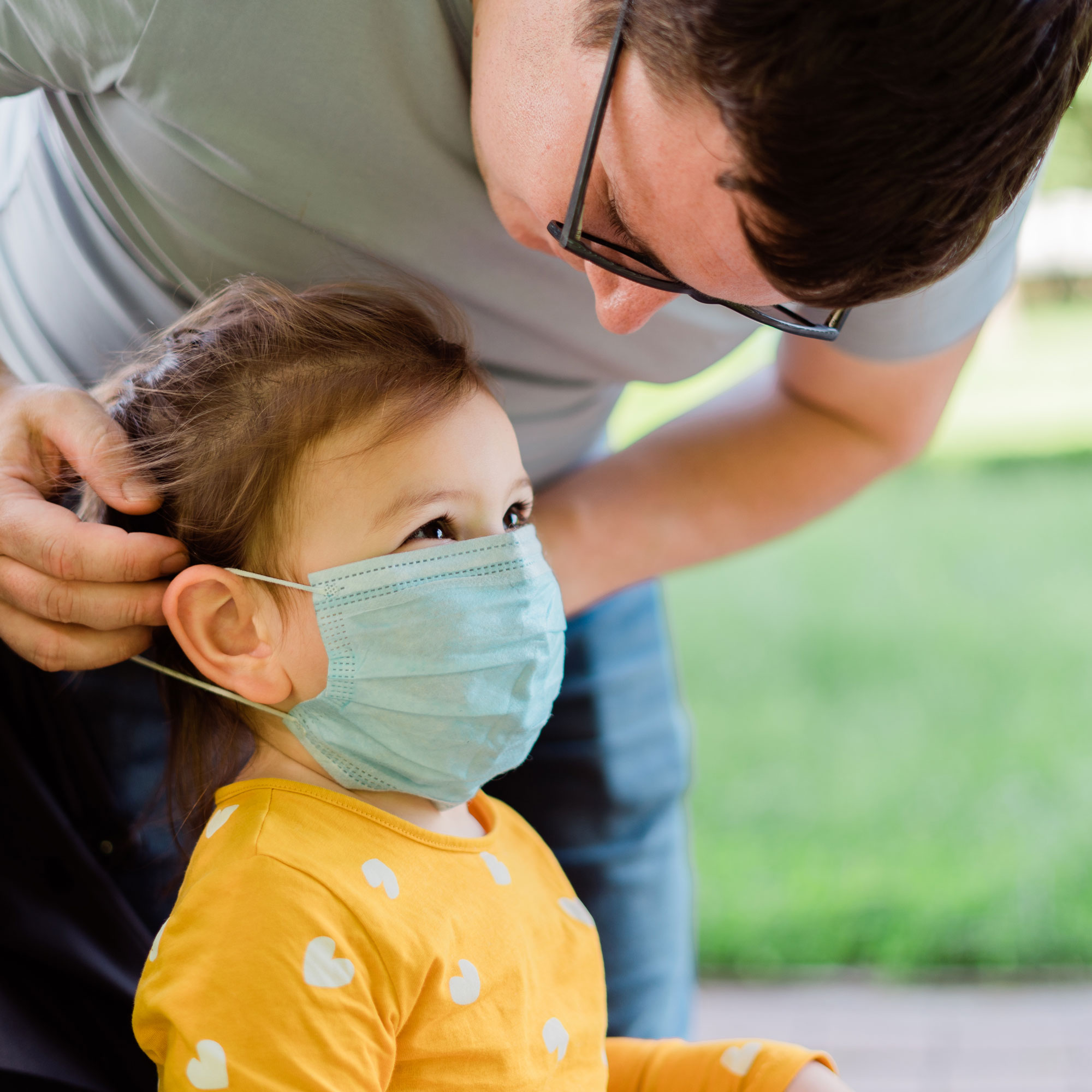 a dad puts a surgical mask on his young daughter