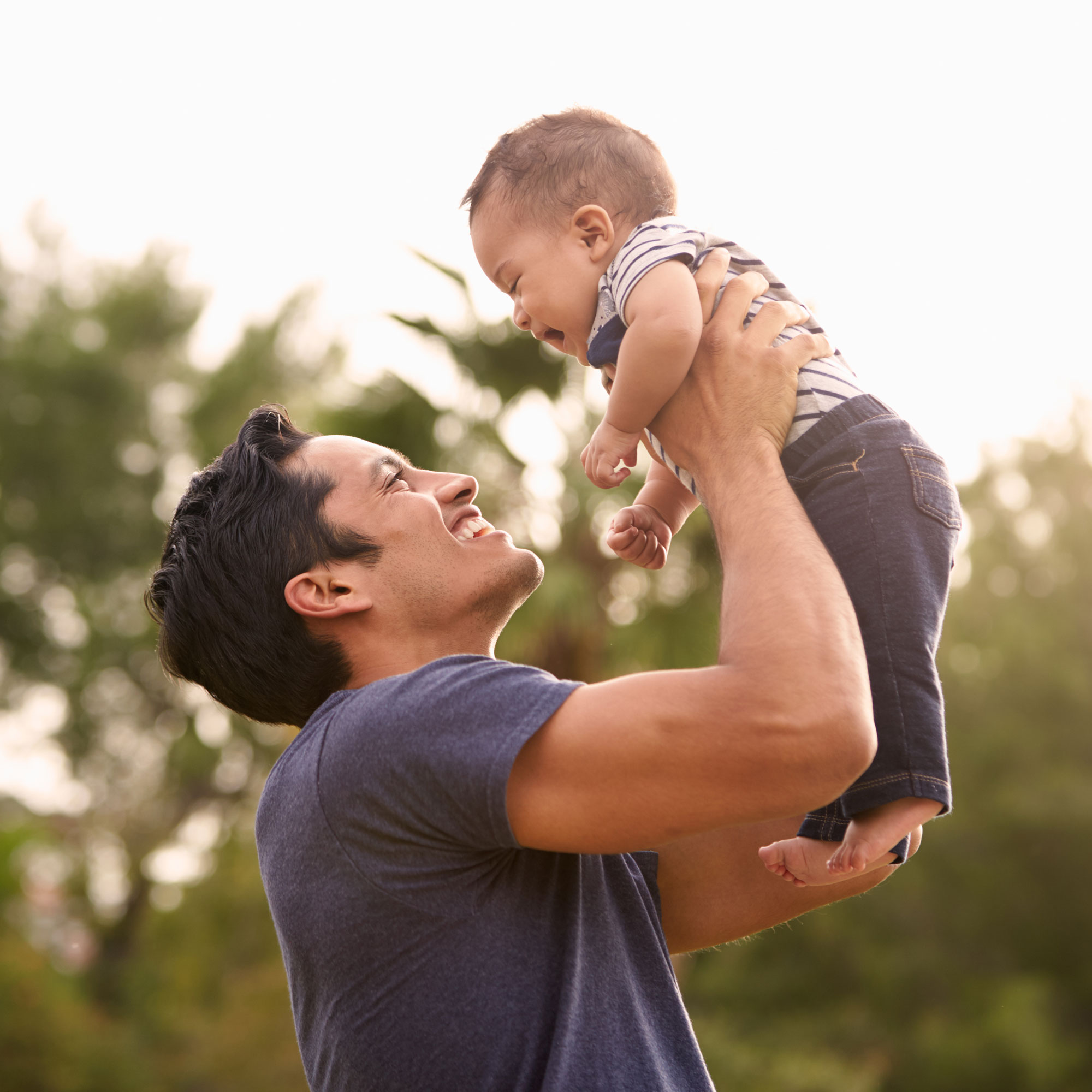 a smiling dad holds his happy baby up in the air