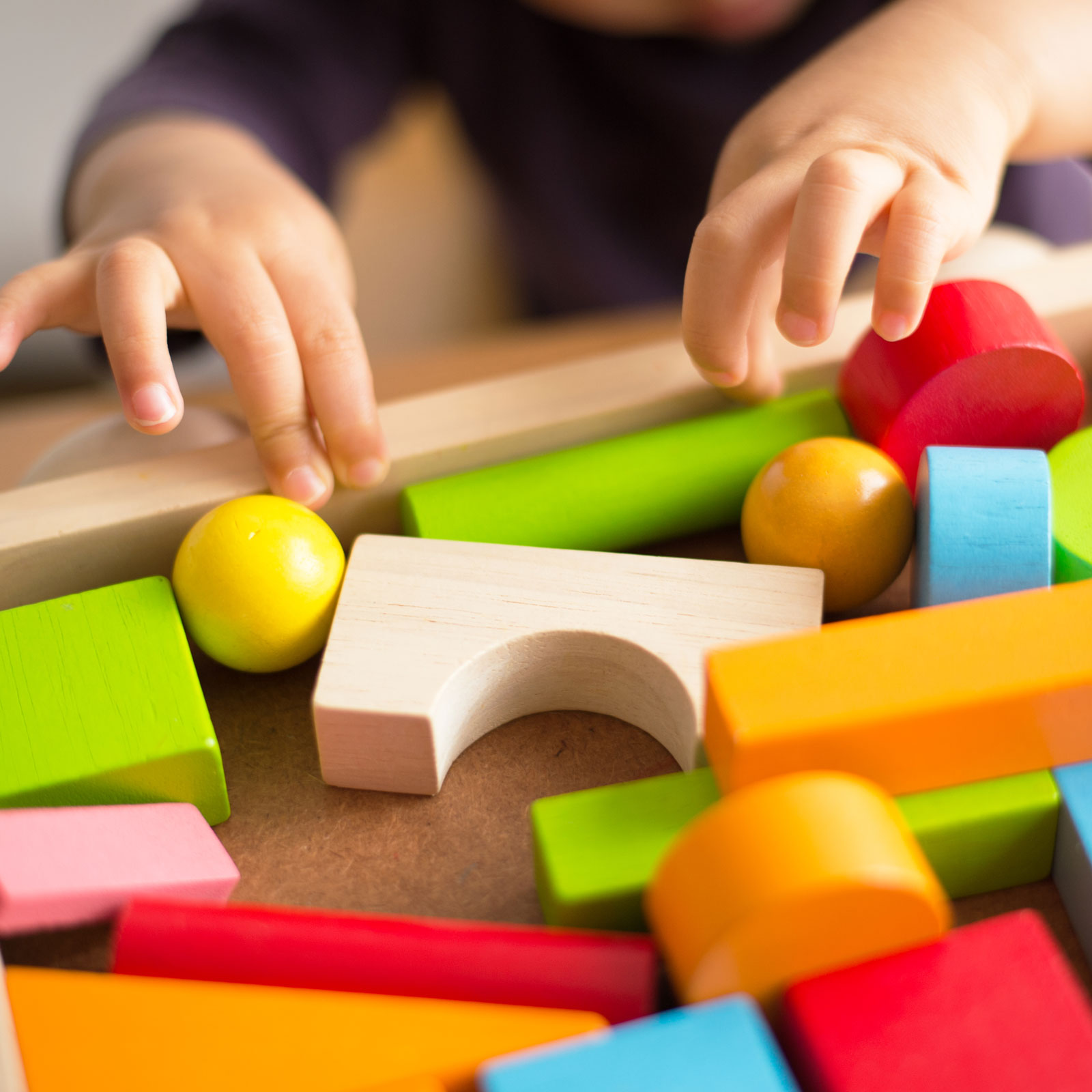 toddler hands playing with colorful blocks