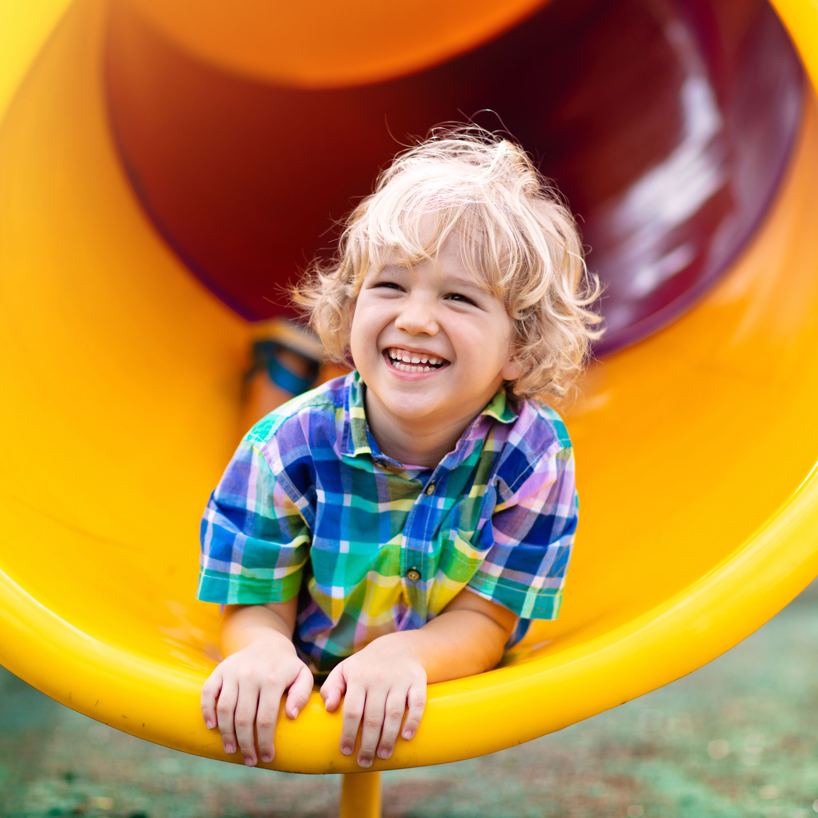 a smiling boy goes down a slide on his belly