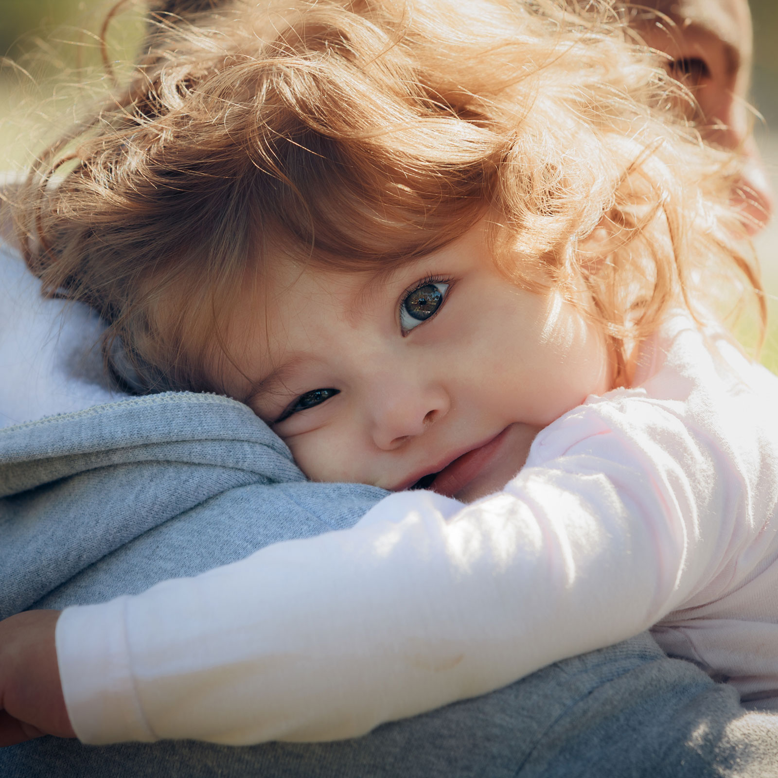 A young girl rests on her dad's shoulder