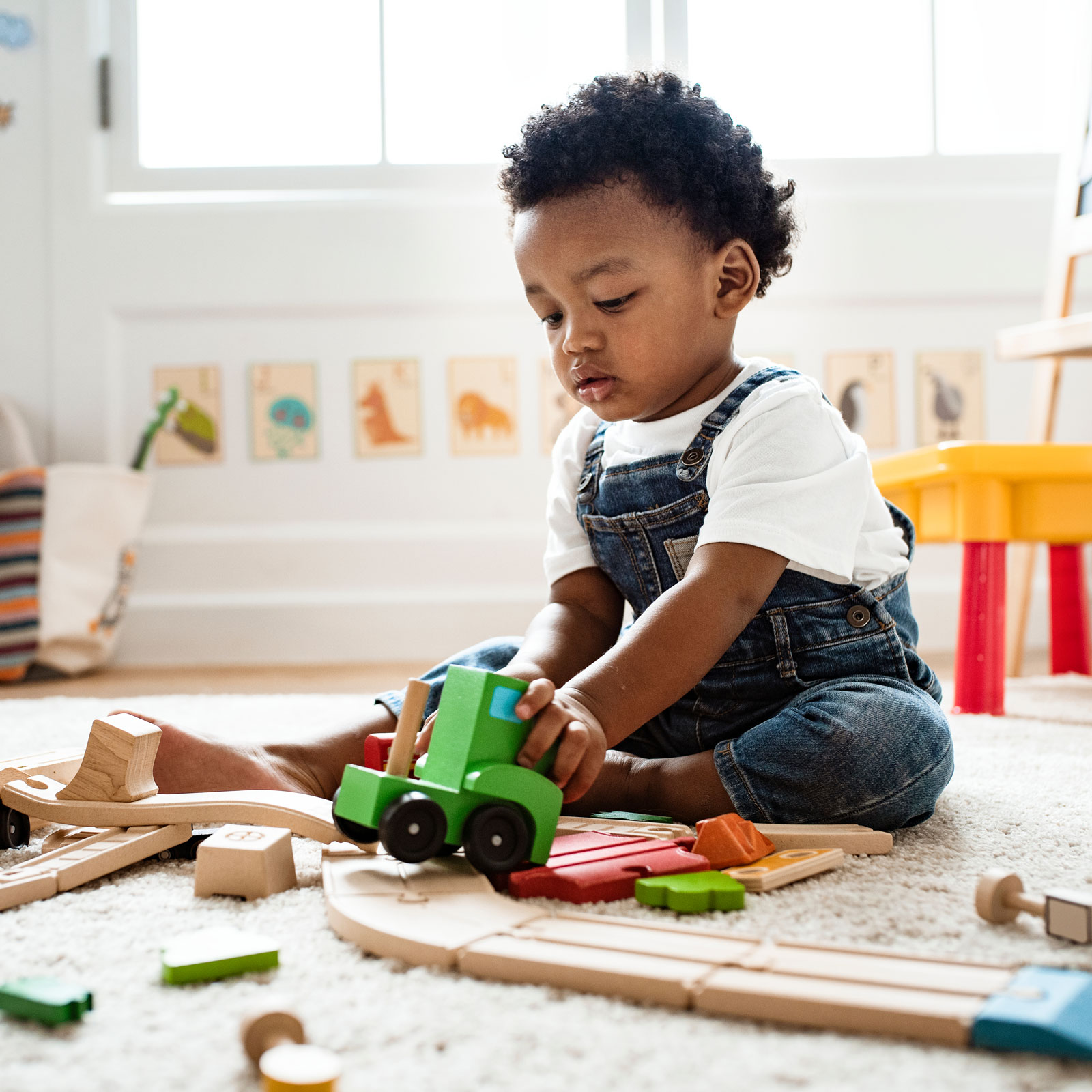 a toddler wearing overalls sits on the floor playing with wooden trains