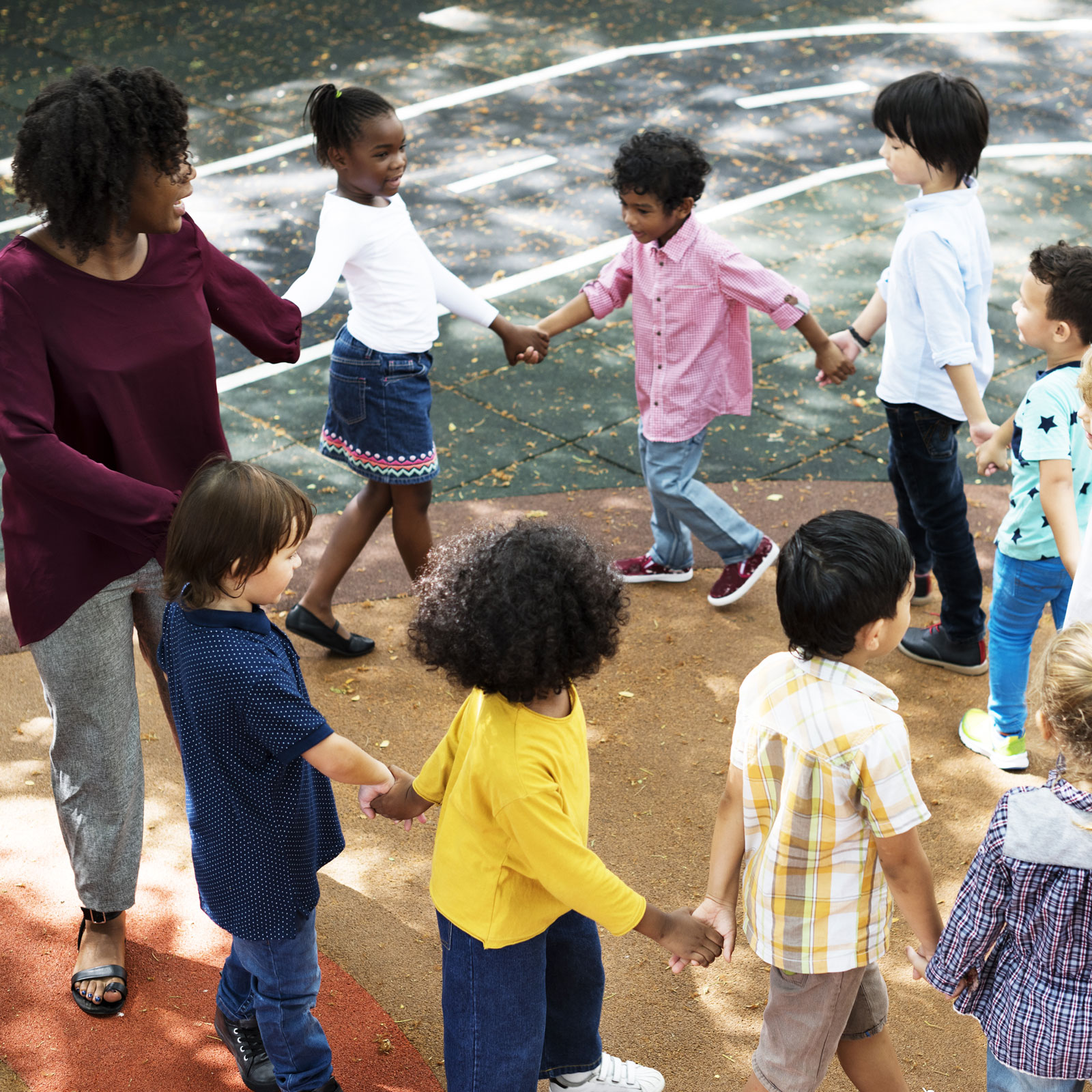 children with their teacher in a circle playing a game on the blacktop at school